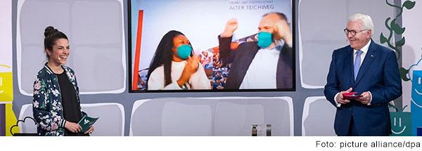 Bundespräsident Frank Walter Steinmeier und Moderatorin Clarissa Correa da Silva stehen lachend vor einer Videowand, au der ein Mann und eine Frau sich anschauen und jubeln. au