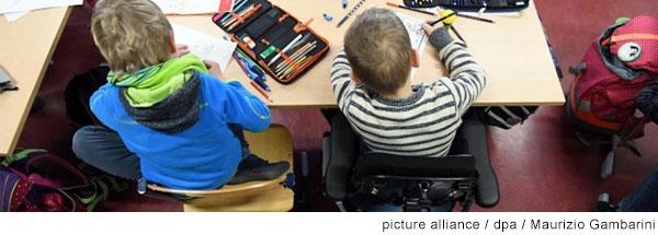 Blick von oben auf zwei Schüler, die an einem Tisch sitzen und arbeiten. Einer der beiden sitzt in einem Rollstuhl.