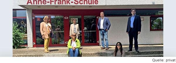 Fünf Menschen stehen und sitzen auf der Treppe vor einem Gebäude, an dem mit roten Buchstaben Anne-Frank-Schule steht.