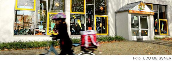 Modernes Schulgebäude der Paul-Maar-Grundschule mit großen Fenstern, an die bunte Buchstaben geklebt sind. Im Vordergrund läuft ein Mädchen durch das Bild, die ein Fahrrad schiebt.