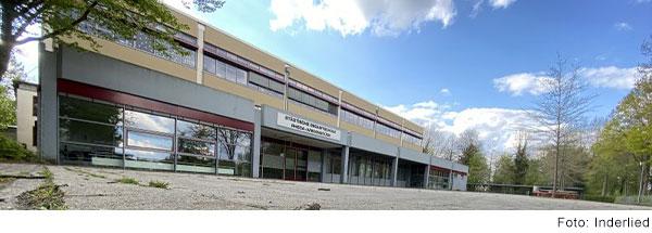 Modernes Schulgebäude mit großem leeren Schulhof.
