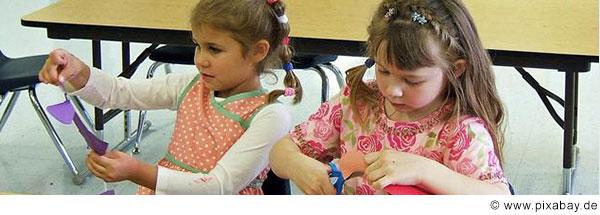 Zwei Mädchen im Grundschulalter sitzen an einer Schulbank und basteln.