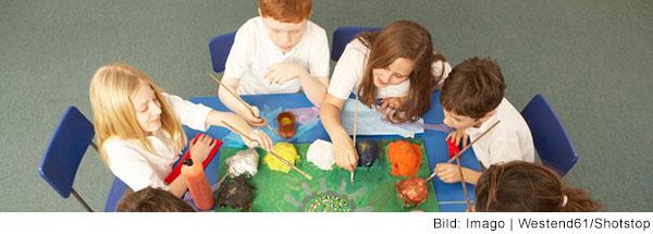 Schulkinder sitzen um einen Tisch und malen gemeinsam an einem großen Bild.