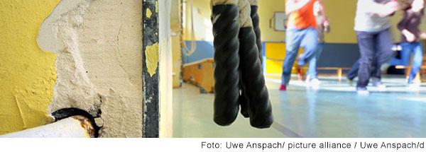 Kinder rennen durch eine Turnhalle. Im Vordergund sihet man eine Wand, von der der Putz bröckelt.