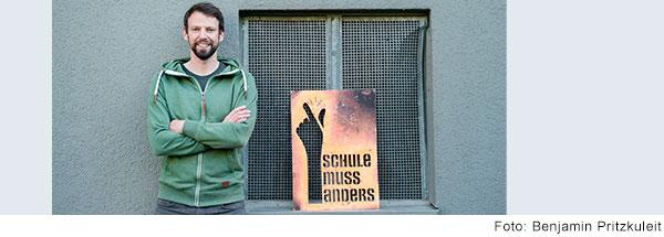 Lachender Mann mit dunklem Haar, Bart und grüner Kapuzenjacke steht mit verschränkten Armen vor einer grauen Hauswand. Auf der Fensterbank neben ihm steht eine Sprühschablone mit der Aufschrift Schule muss anders.