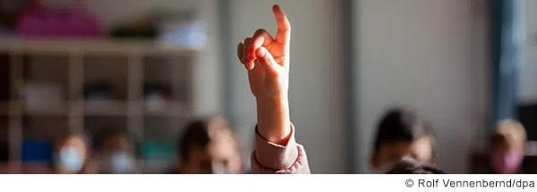 Nahaufnahme von Hand und Arm einer aufzeigenden Schülerin.