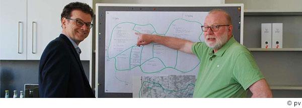 Zwei Männer stehen vor einer Tafel mit einer skizzierten Landkarte.