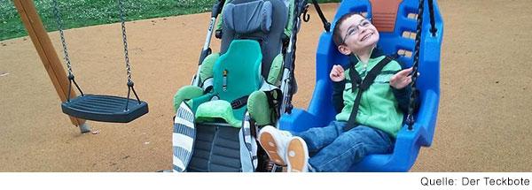 Junge mit Behinderung sitzt auf einer Schaukel mit Rückenlehne, schaut in den Himmel und lacht.