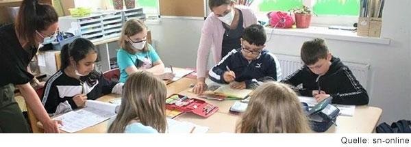 Sechs Kinder sitzen um einen Schultisch und Schreiben. Zwei Frauen sprechen mit einzelnen Kindern.