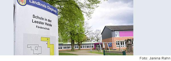 Schulgebäude mit Hof. Im Vordergrund steht ein Schild mit der Aufschrift: Landkreis Diepholz, Schule in der Leester Heide, Förderschule