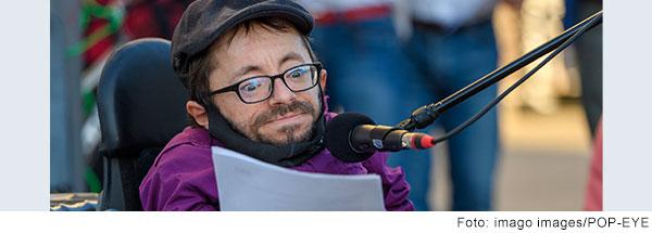 Raul Krauthausen mit dunkler Mütze und lila Hemd  spricht in ein Mikrofon.