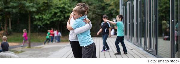 Zwei Schulkinder umarmen sich auf dem Schulhof. (Foto: imago stock)