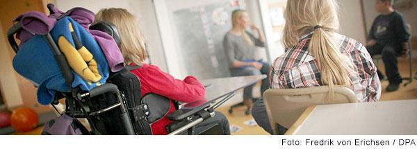 Eine Lehrerin und mehrere Schüler und Schülerinnen sitzen im Klassenzimmer in einem Kreis. Eine Schülerin sitzt in einem Rollstuhl.