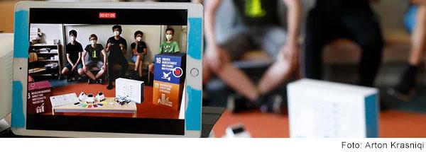 Auf einem Tablet sieht man einen Erwachsen und 4 Schüler in einem Klassenzimmer präsentieren. (Foto: Arton Krasniqi)