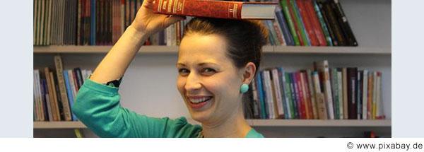Eine Frau  mit dunklen zurückgesteckten Haaren legt sich ein Buch auf den Kopf und lacht. (© www.pixabay.de)