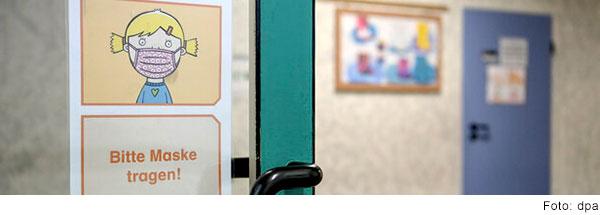 """Auf einer Tür im Schulflur klebt ein Schild mit der Aufschrift """"Bitte Maske tragen"""". (Foto:dpa)"""