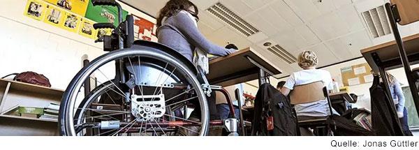 In einem Klassenzimmer sitzt im Vordergrund eine Schülerin im Rollstuhl.