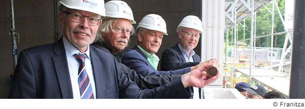 Vier ältere Herren mit weißen Bauhelmen stehen nebeneinander auf einer Baustelle und lachen in die Kamera.