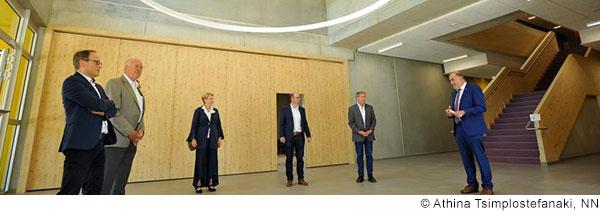 Sechs Männer und eine Frau in Anzügen stehen mit großem Abstand zueinander in einem modernen Gebäude. Einer der Männer hält eine Rede. (© Athina Tsimplostefanaki, NN)