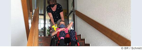 Eine Frau zieht ein Mädchen im Rollstuhl die Treppe hoch.