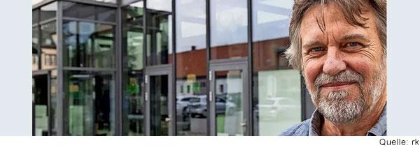 Ein Mann mit angegrautem Bart steht vor einer Glasfassade und lacht selbstbewusst in die Kamera.