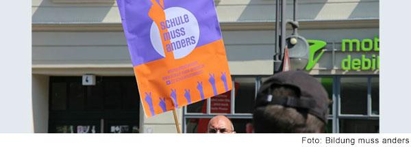 """Mann hält Banner mit der Aufschrift """"Schule muss anders""""."""
