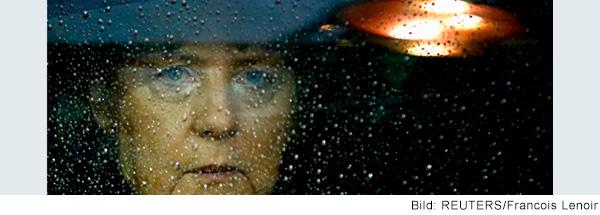 Frau Merkel schaut ernst durch eine mit Regentropfen bedeckte Scheibe.