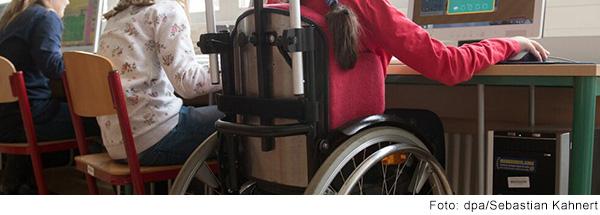 Drei Schüler*innen sitzen an einem Tisch in der Schule. Eine Schülern sitzt in einem Rollstuhl.