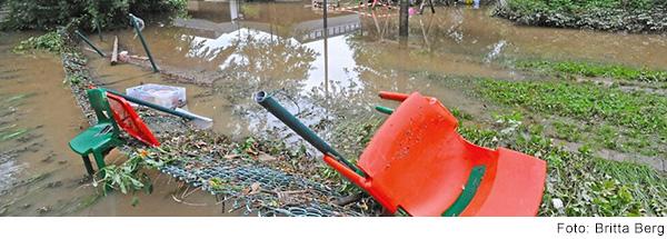 Ein roter Stuhl liegt auf einem überfluteten Schulhof.