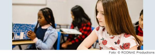 Kinder sitzen im Klassenzimmer an Tischen.