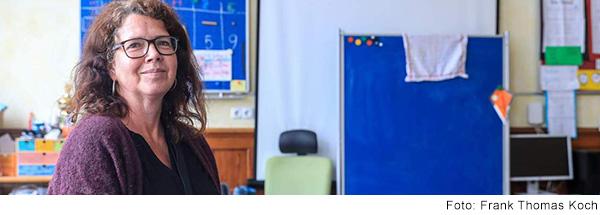 Eine Frau mit langen lockigen braunen Haaren und dunkler Brille sitzt im Klassenzimmer und lacht.