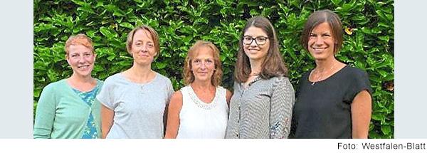 Fünf Frauen unterschiedlichen Alters stehen nebeneinander und lächeln.