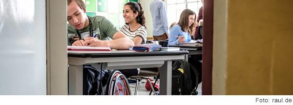 In einem Klassenzimmer sitzen unterschiedliche Schüler*innen und arbeiten. Ein Schüler sitzt im Rollstuhl.