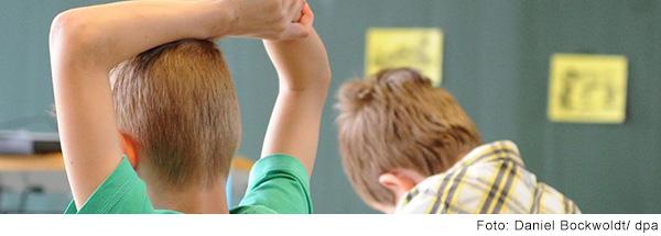 Zwei Jungen sitzen an einem Tisch im Klassenzimmer, einer meldet sich.