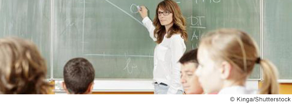 Lehrerin schreibt an die Tafel.