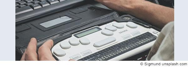 Foto von einer Braillerzeile, die vor einer regulären Computertastatur steht. Man sieht die Hände einer Person, die die Braillezeile benutzt.