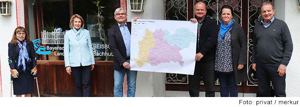 Drei Frauen und drei Männer stehen vor einem Gebäude. Zwei Männer in der Mitte halten eine Landkarte hoch.