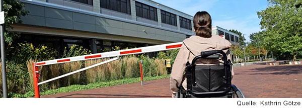 Eine Frau im Rollstuhl steht vor einer Schranke.