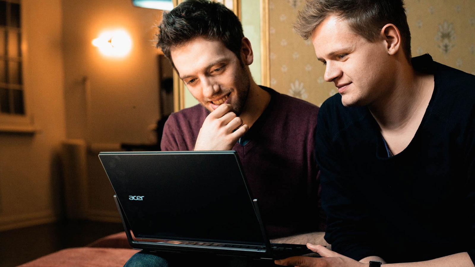 Dennis und Christian sitzen am Laptop