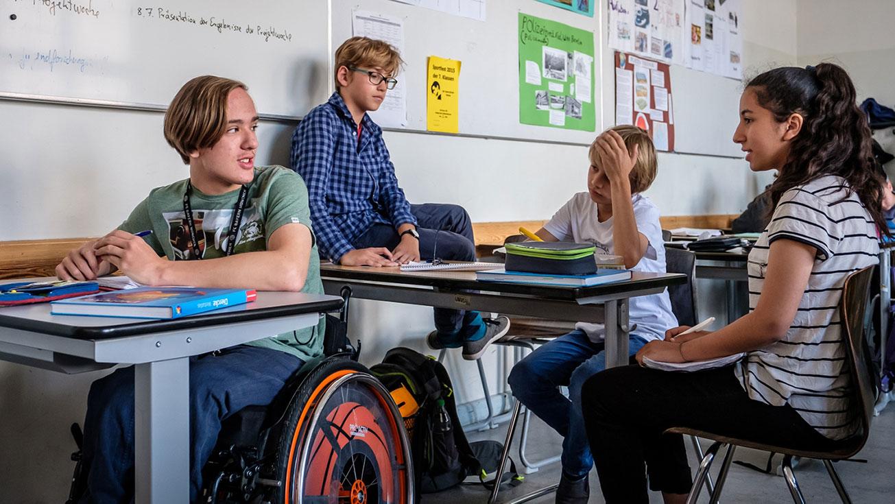 Klassenszene mit Jungem im Rollstuhl und anderen Schüler*innen