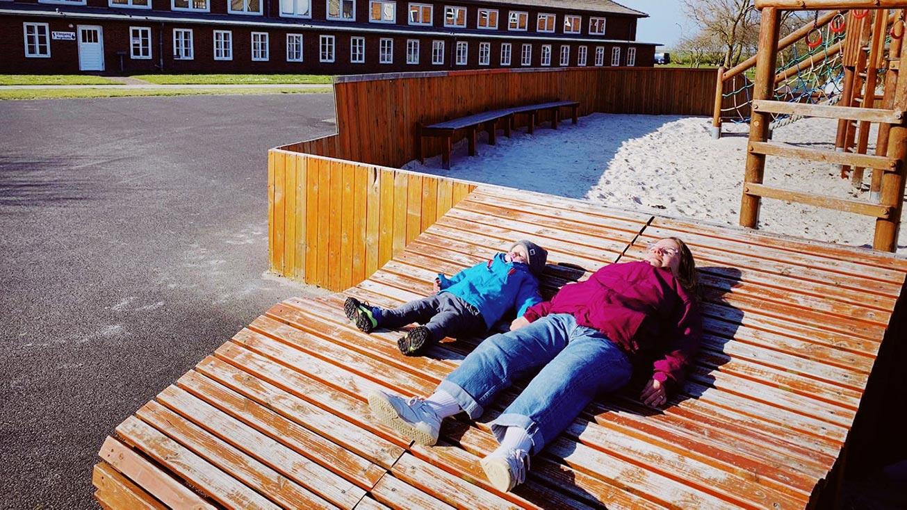 Ninia und Sohn liegen nebeneinander auf einer Holzrampe am Spielplatz