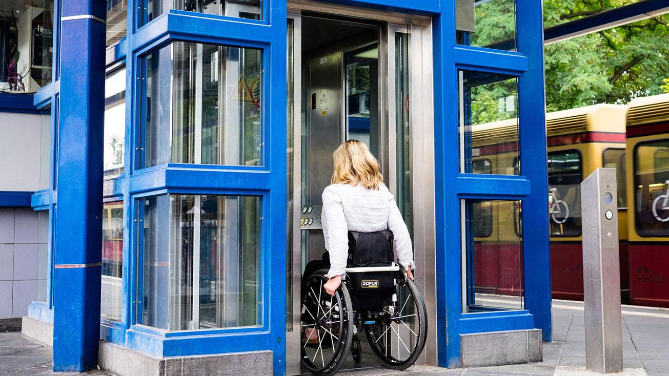 Frau im Rollstuhl benutzt Aufzug auf einem Bahnsteig
