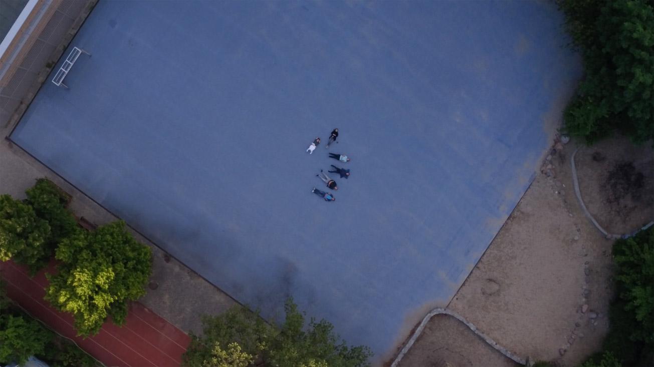 Luftaufnahme der sechs Hauptfiguren, die sich auf dem Schulhof hingelegt haben.