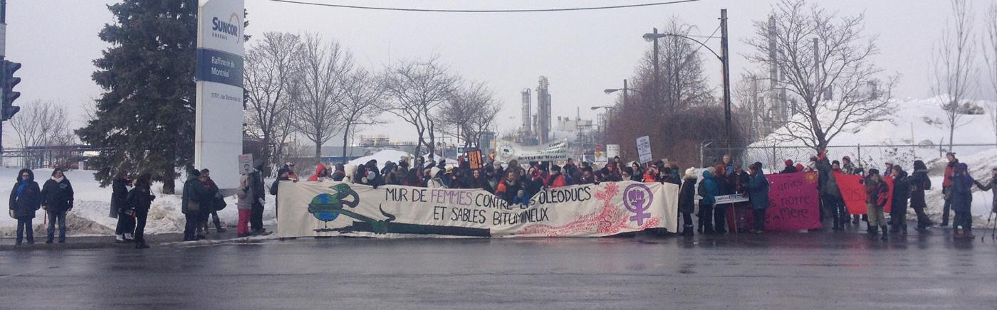 """Des femmes devant Suncor à Montréal portant une large bannière """"Mur des femmes contre les oléoducs et sables bitumineux"""""""