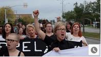 des femmes dans en action la rue avec une bannière, les poings levés, scandant des slogans