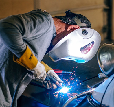 welder working on car