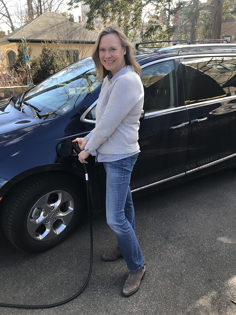 Mothers Out Front volunteer plugs in her electric Chrysler Pacifica