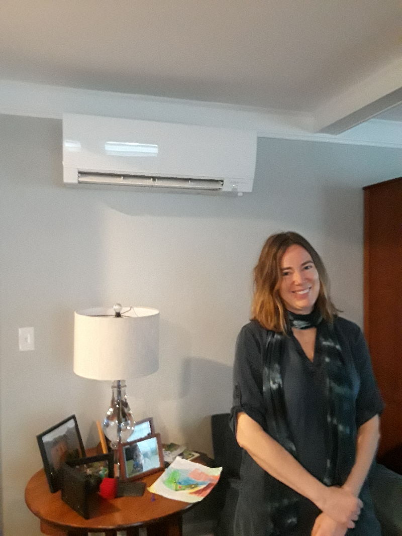 Mothers Out Front member stands in front of her mini-split heat pump