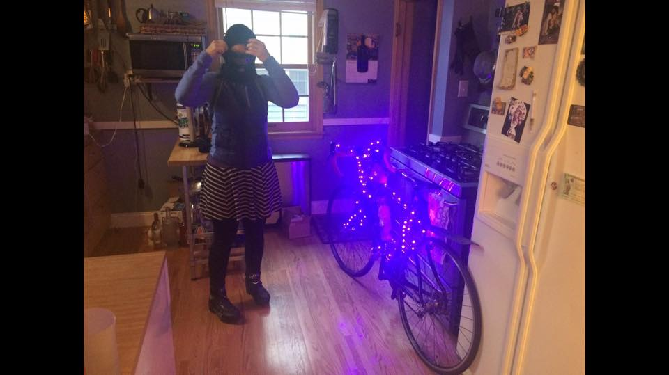 Person wearing winter gear standing inside next to a bike with string lights on it