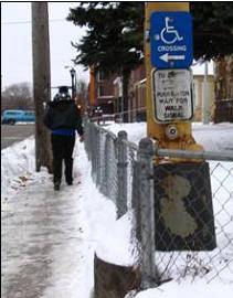 Snowy narrow sidewalk and push button (City_of_Minneapolis)